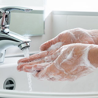 Photo of person washing their hands with soap and water
