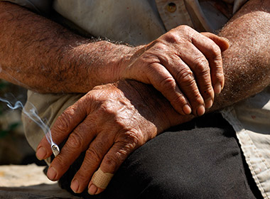 Photo of weathered working hands holding a cigarette
